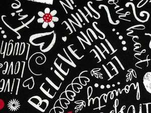 Close up of black cotton fabric that is covered with happy words.