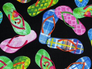 Close up of black fabric that is covered with blue, green and pink flip flops.