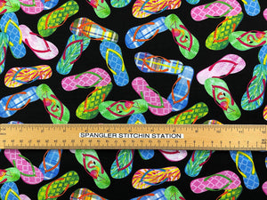 Ruler on black fabric that is covered with blue, green and pink flip flops.