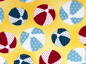 Close up of yellow fabric that is covered with blue and red beach balls.