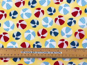 Ruler on yellow cotton fabric that is covered with blue and red beach balls.