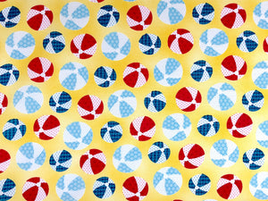 Yellow cotton fabric covered with blue and red beach balls.