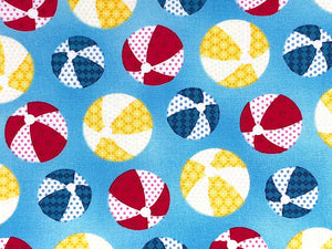 Close up of blue cotton fabric that is covered with blue, yellow and red beach balls.