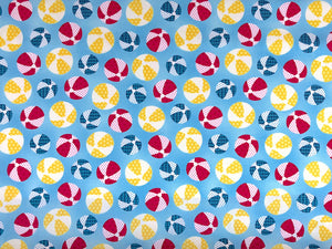Blue cotton fabric covered in beach balls that are yellow, blue and red.