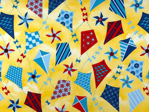 Yellow cotton fabric covered with kites that are blue and red.