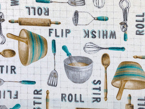 Close up of cotton fabric covered with rolling pins, bowls, spoons, whisks, spatulas and more.