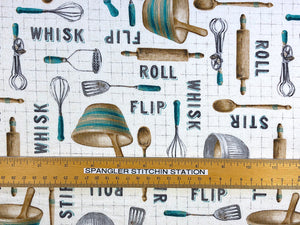 Ruler on cream colored cotton fabric covered with kitchen utensils.
