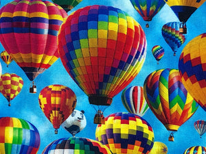 Close up of blue fabric covered with hot air balloons.