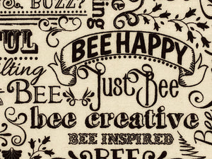 Close up of cream colored cotton fabric covered with words such as bee happy and bee creative.