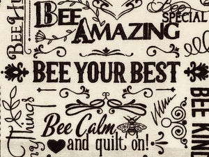 Cream cotton fabric covered with positive words such as bee your best and be calm and quilt on.