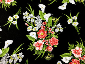 Close up of black cotton fabric that is covered with white and peach colored flowers.