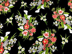 Black cotton fabric covered with white and peach flowers and green leaves.