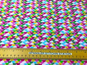 Ruler on cotton fabric that is covered with half circles in various colors