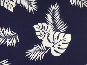 Close up of tropical leaves on a blue background.