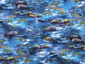 Close up of cotton fabric that has a river scene of water, mossy rocks and sticks.