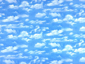 Cotton Fabric covered with white clouds in a blue sky.