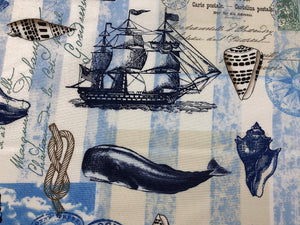 Close up of sea shell, whale, and ship on cotton nautical fabric.
