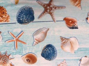 Close up of cotton fabric that is covered with sea shells.