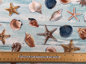 Ruler on cotton fabric that is covered with sea shells.
