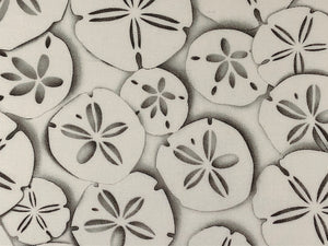 Close up of white fabric covered in sand dollars.
