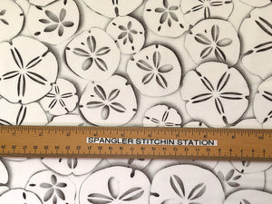 Ruler on white fabric that is covered in sand dollars.
