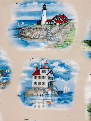 Close up of cream colored cotton fabric that is covered with lighthouses and boats.