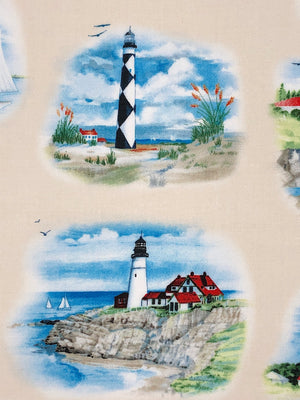 Close up of cream colored fabric covered with lighthouses, sand, boats and flowers.