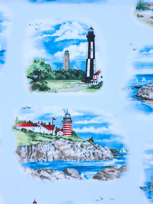 Close up of light blue fabric covered with lighthouses.