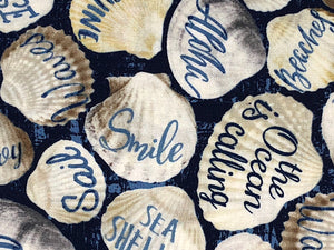 Close up of seashells covered with words such as smile, the ocean is calling and more.