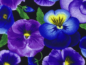 Close up of purple and blue pansies with yellow centers.