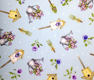 Close up of light blue cotton fabric covered with watering cans with pansies, bird houses and more.