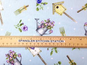Ruler on light blue cotton fabric covered with bird houses, pansies and watering cans full of pansies.