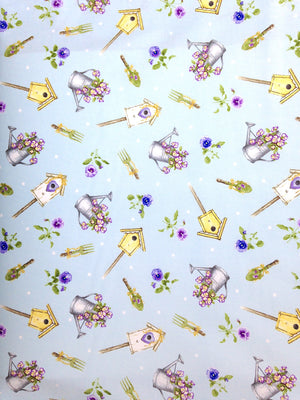 Light blue cotton fabric covered with pansies, bird houses and watering cans with flowers.