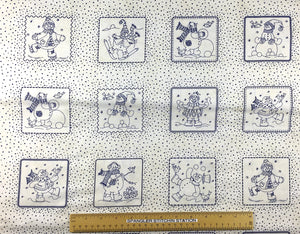 Ruler on cotton fabric that is covered with snowmen in squares.