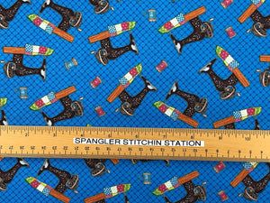 Ruler on Blue cotton fabric that is covered with sewing machines.