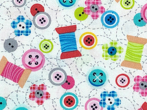 Close up of white cotton fabric that is covered with spools of thread, buttons and small flowers.