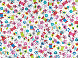 White Cotton Fabric covered with spools of thread, buttons and small flowers.