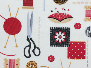 Close up of white cotton fabric covered with scissors, buttons, pincushions and other sewing notions.