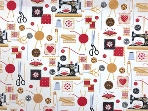 White cotton fabric covered with sewing machines, scissors and other sewing notions.
