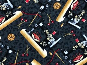 Close up of black cotton fabric covered with sewing machines.