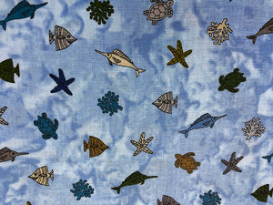 Close up of cotton fabric covered with starfish, coral, turtles and other sea life.