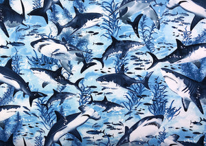 Close up of cotton fabric that is covered with swimming sharks.