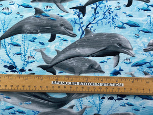 Ruler on fabric that is covered with swimming dolphins.