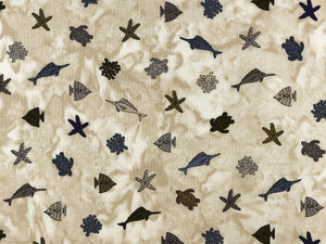 Tan fabric covered with starfish, turtles swordfish and more.