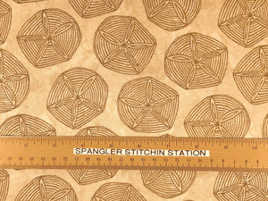 Ruler on beige cotton fabric that is covered with sand dollars.