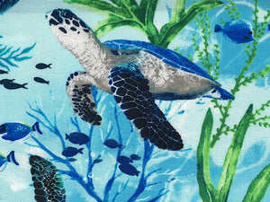 Close up of swimming sea turtle on cotton fabric.