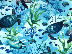 Cotton fabric that is covered with swimming sea turtles and water plants.