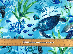 Ruler on fabric that is covered with swimming sea turtles.