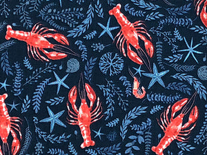 Close up of blue cotton fabric covered with red lobsters and plants found in the sea.