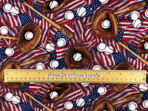 Ruler on cotton fabric that is covered with flags, baseballs, baseball bats, baseball gloves.